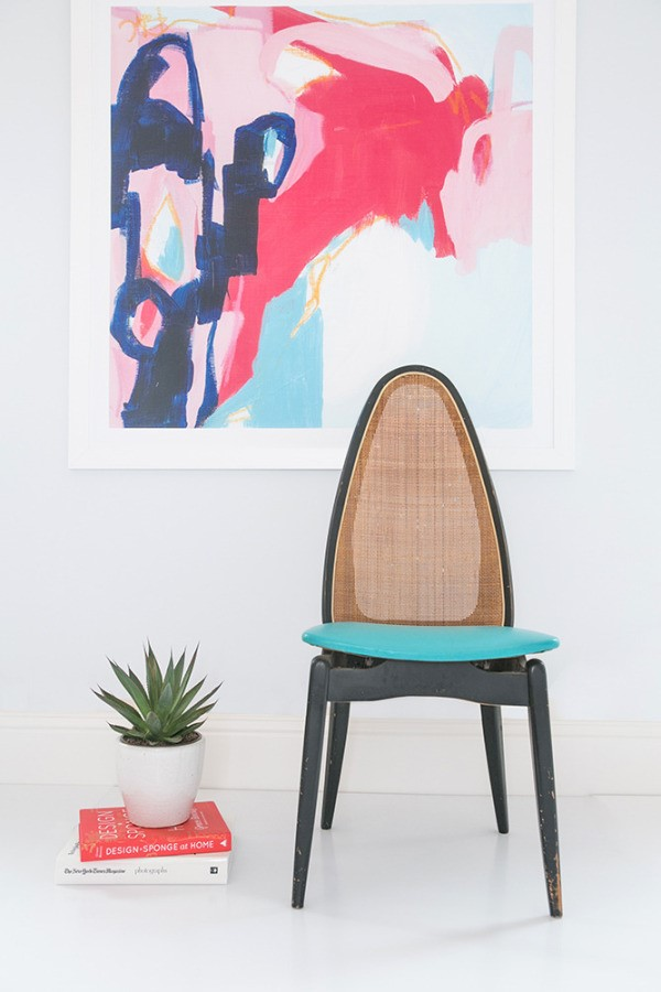 a minimalist room with a black and blue chair, a pink abstract painting and a small green summer succulent