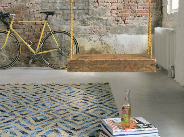 an industrial loft interior with a vintage bicycle and a blue tika rug