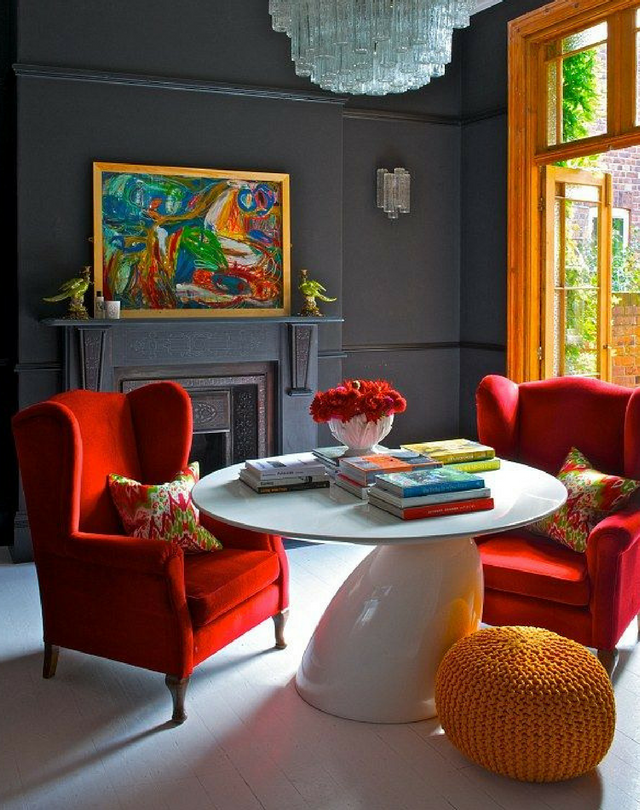 dark colours muted grey coloured walls in an unconventional dining room with red chairs