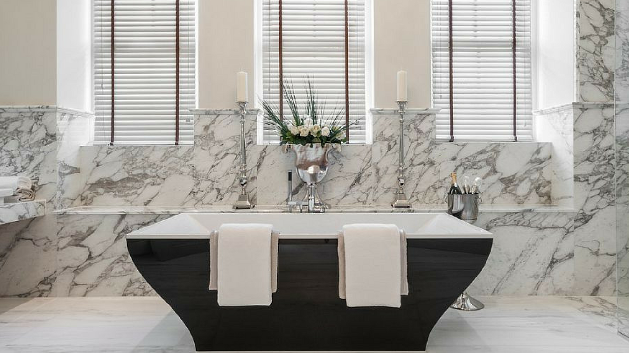 dark colours marble walls and black bathtub in a large bathroom