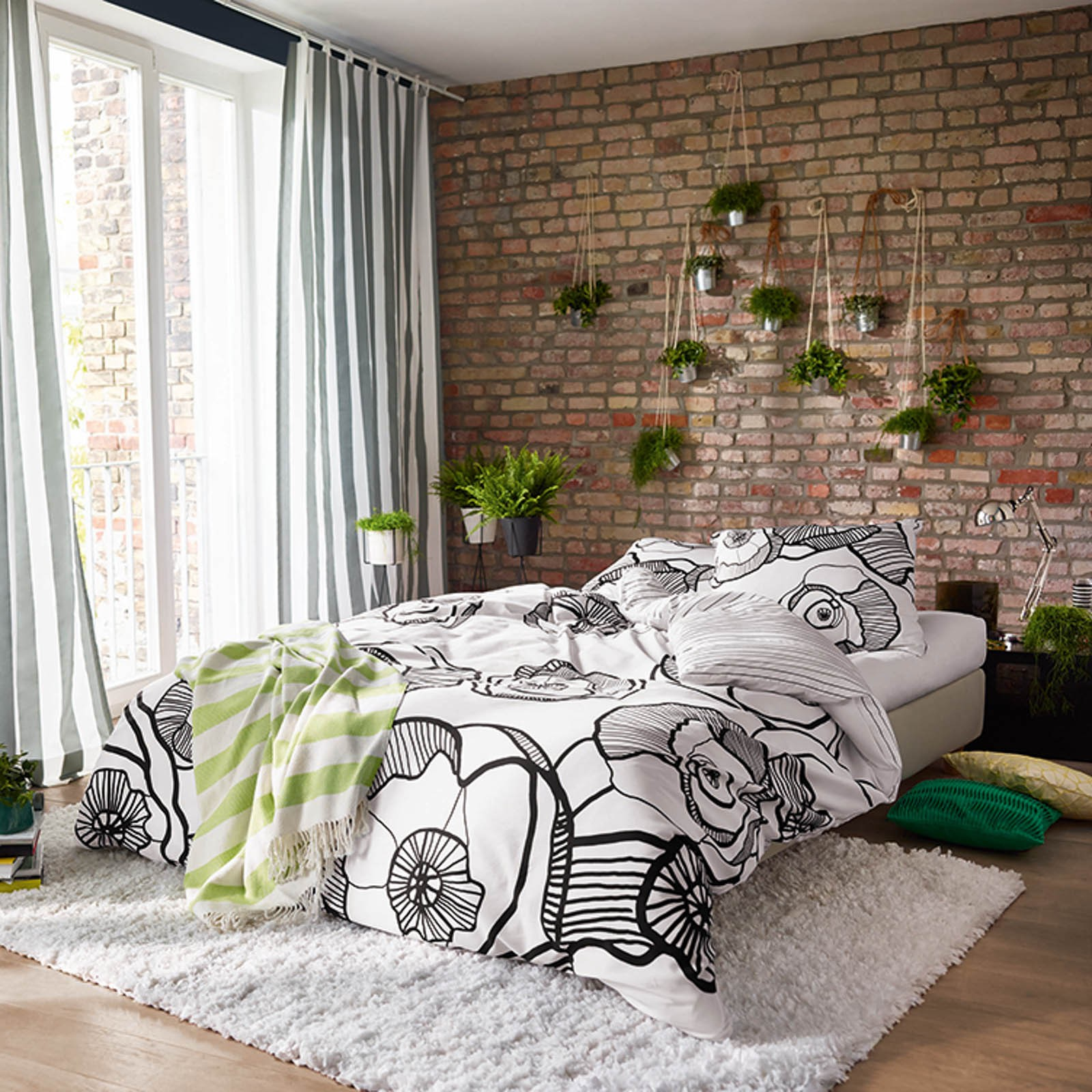 beddroom with bed near window with exposed brick wall