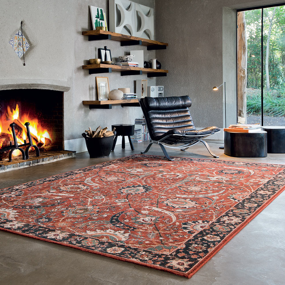traditional rug in concrete style living room next to a chair and a roaring fireplace