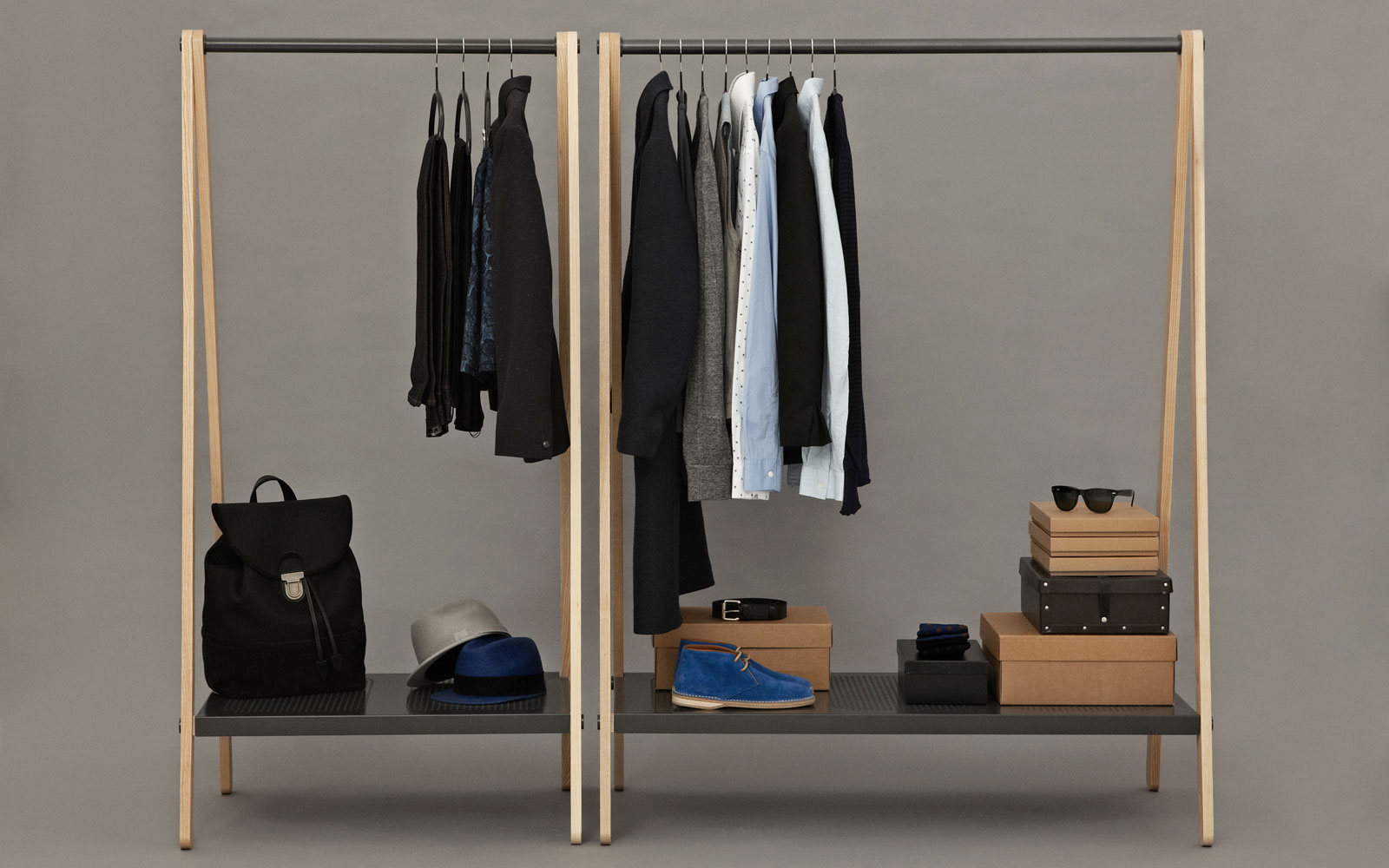 clothing rack with shoes, shirts, and sunglasses in a plain room