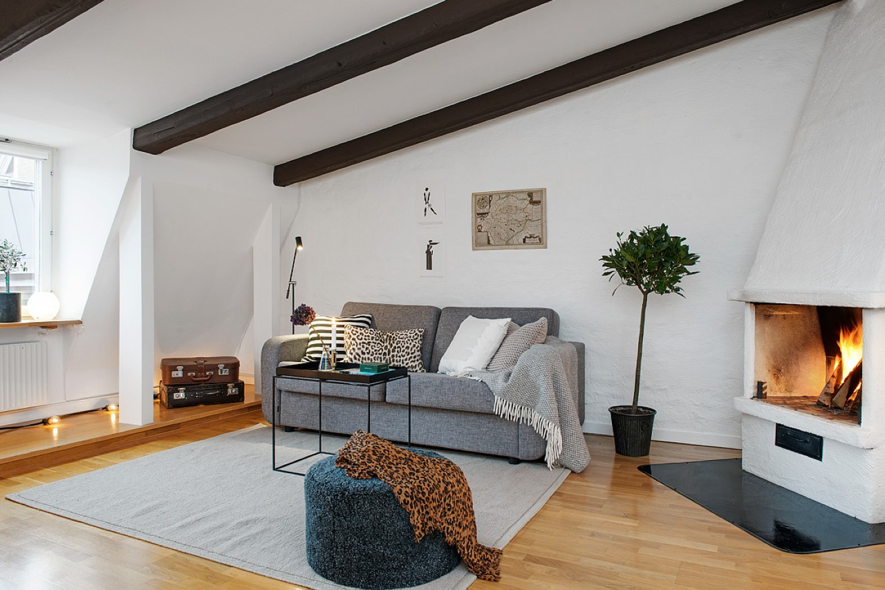 scandinavian interior with a couch and fireplace a pouffe