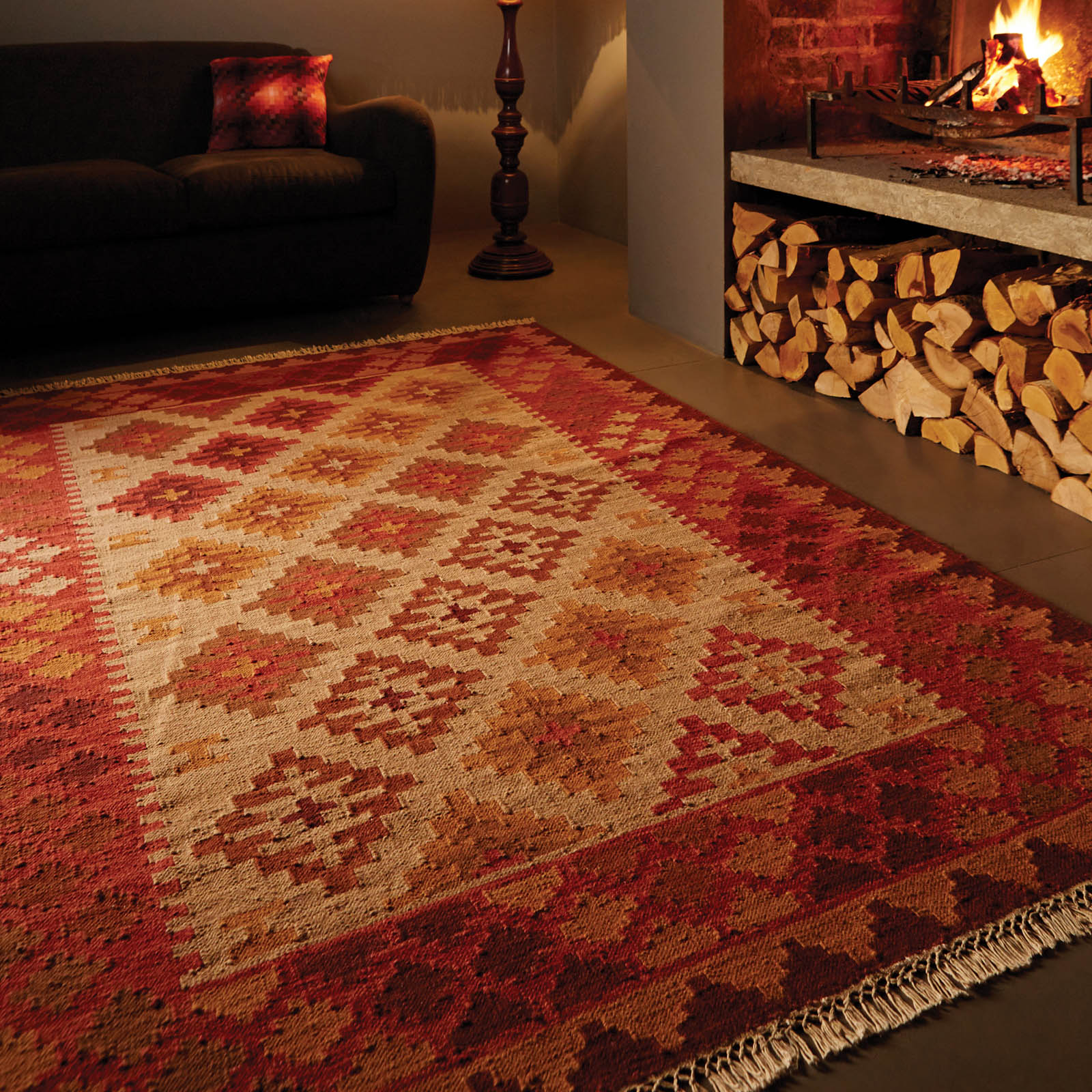 kilim rug on concrete floor next to fireplace and black couch
