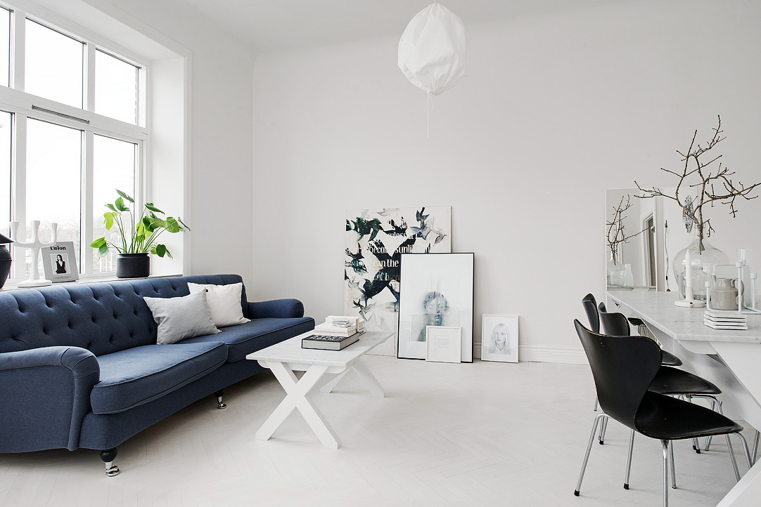scandinavian interior with a blue couch and a table with a stack of books on top