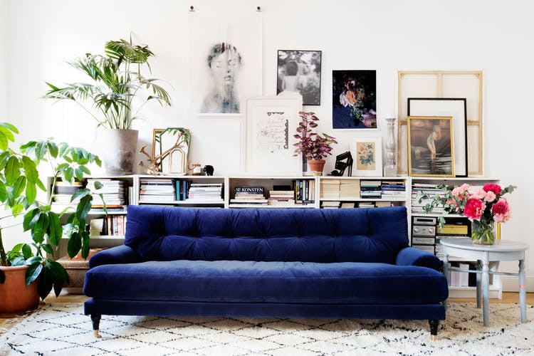 dark blue velvet couch in a rustic overly decorated interior