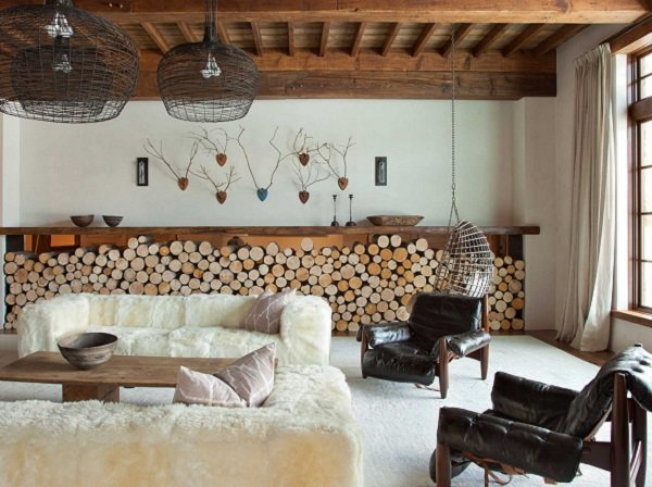 rustic interior design with firewood, exposed beams and a cream couch among other furniture