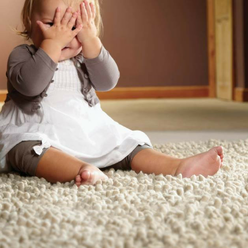 beige shaggy rug with a toddler sat on it