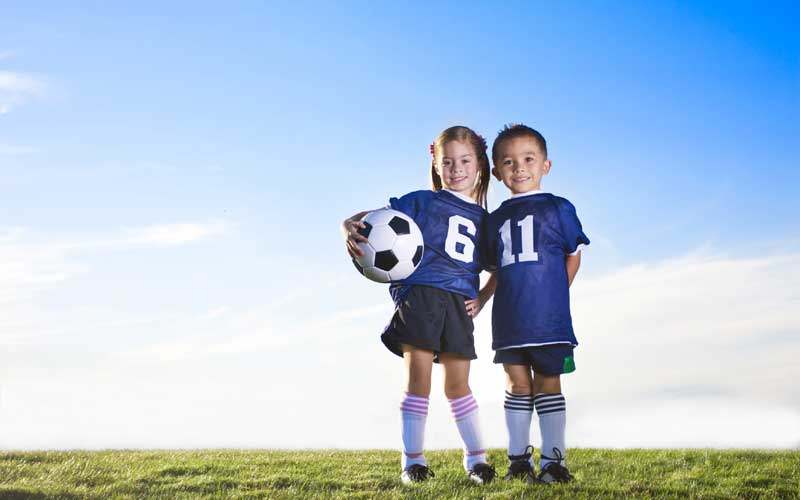 2 young children holding a football