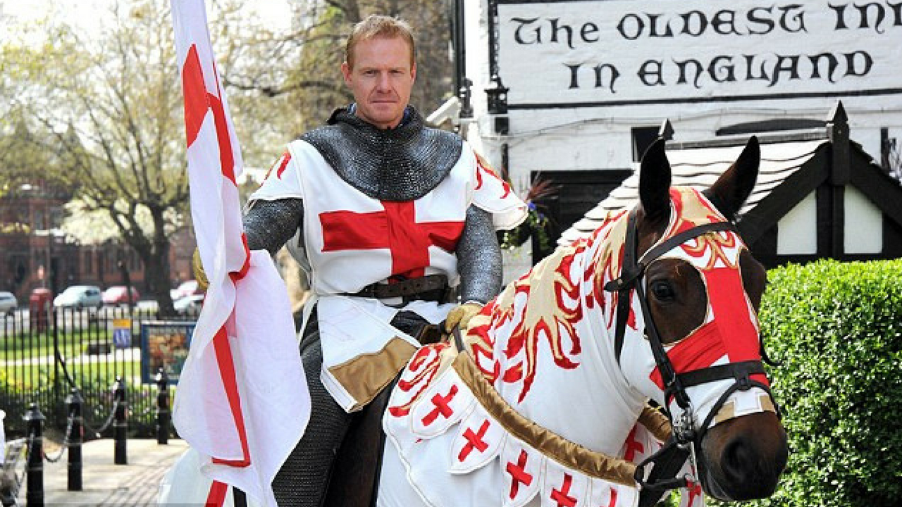 St. George's Day man dressed in medieval costume riding a horse and holding an England flag