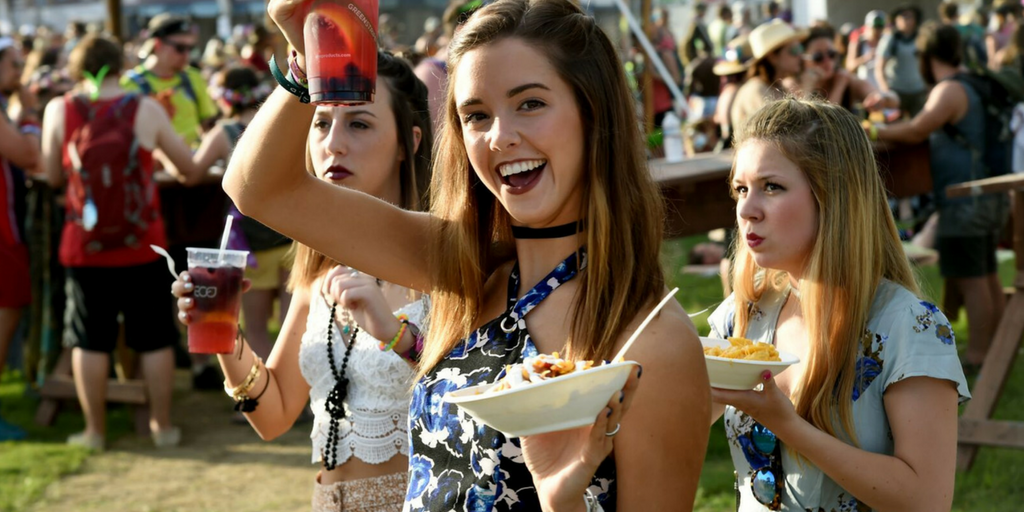 festival essentials girl smiling whilst holding her chips