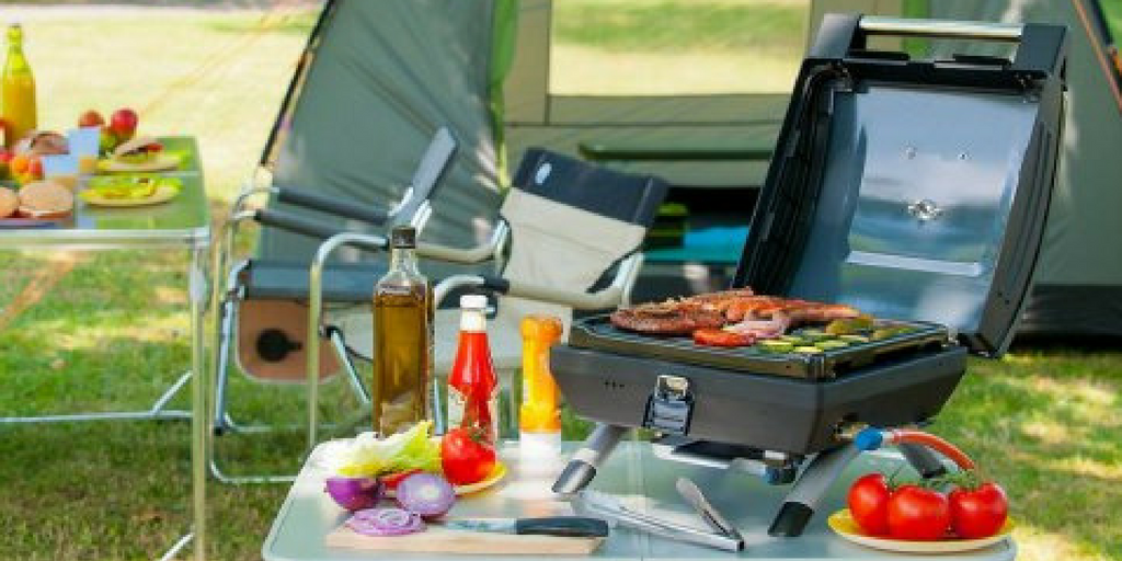 festival essentials BBQ set up next to a camping site