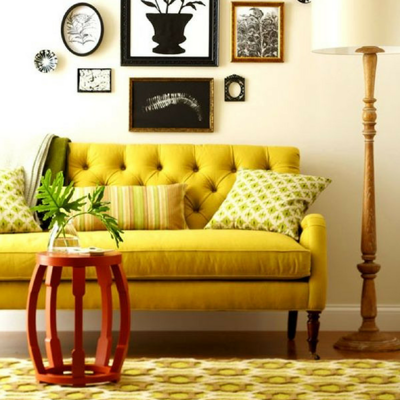 Yellow sofa, throw pillows and rug in a large living room setting