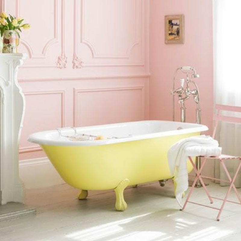 Yellow and bright bathtub in a pastel pink coloured bathroom
